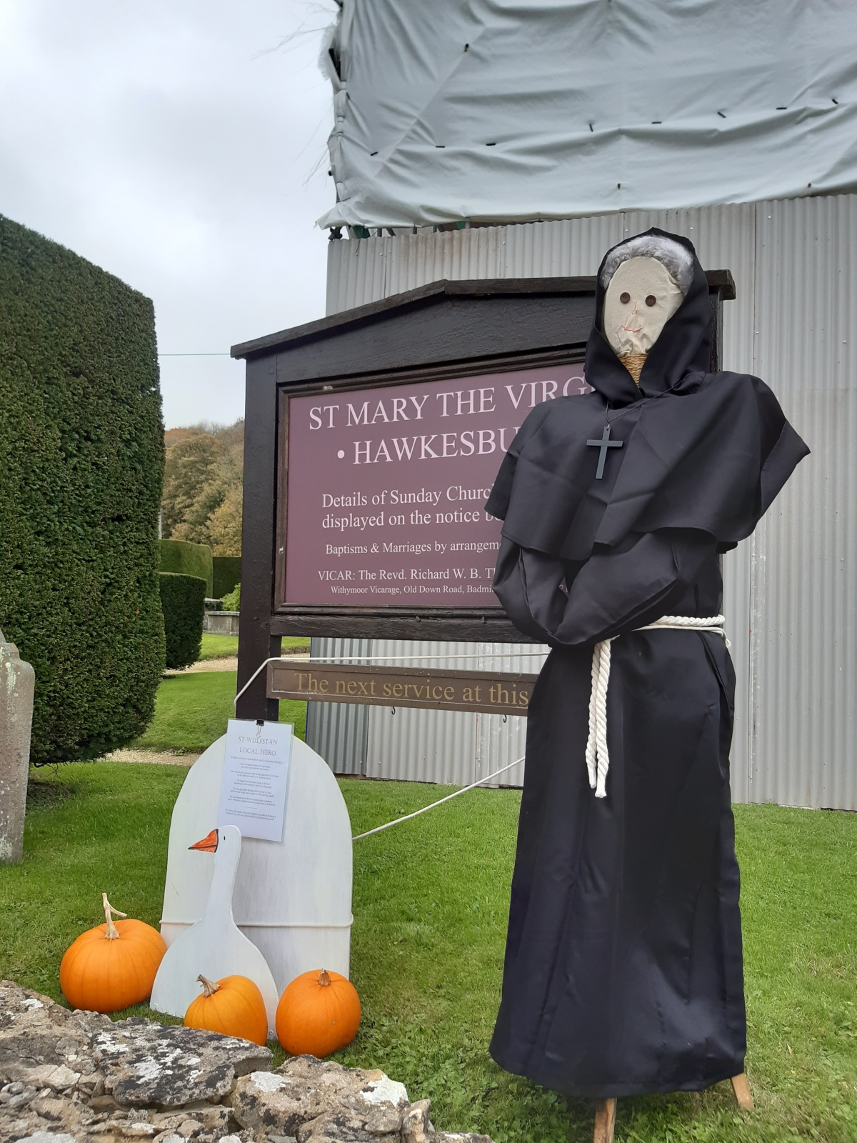 photo of scarecrow with wooden goose and pumpkins outside church