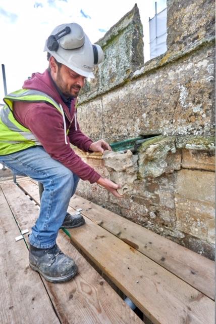 photo of stonemason returning hunky punk to tower